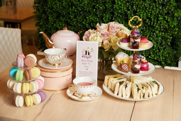 A table with a tea pot, cup and saucers, a platter f sandwiches and cakes and a display of macarons