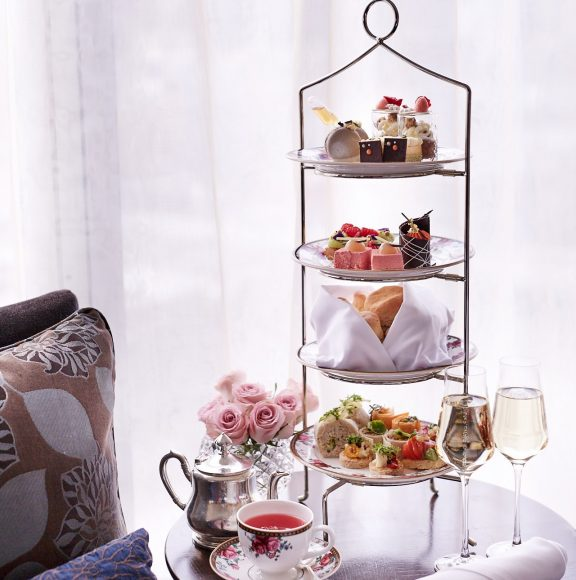 A high tea display of cakes, snadwiches and other sweet desserts with a glass of sparkling wine and a pot of tea, cup and saucer on a table
