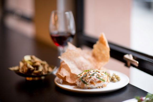 A selection of small dishes and a glass of wine on a window ledge