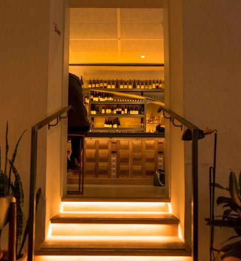 A lighted up indoor stairs leading to a doorway which reveals a bar