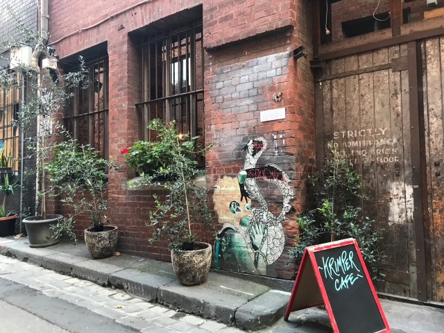 A blackboard sign set up outside a building with street art in a laneway