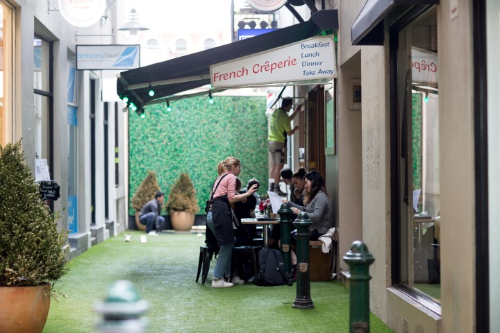 People sitting outside a cafe in a laneway