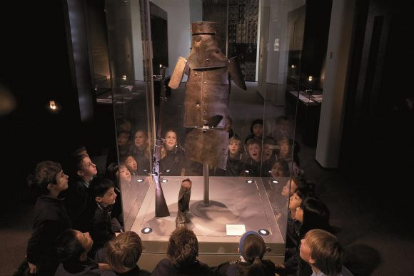 A group of children around a square glass display box, which contains one of the tin suits worn by bushranger Ned Kelly
