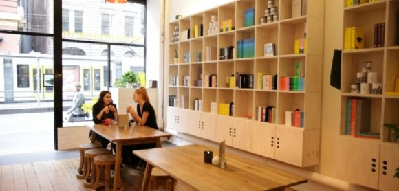 Two women sitting at a table in a cafe drinking coffee, with a bookshelf behind them