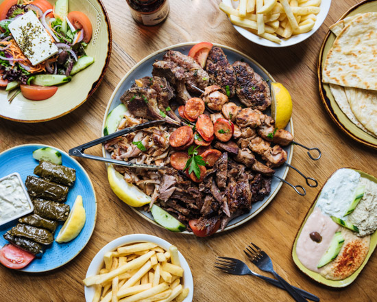 A large plate of greek meat with platters pf salad and chips around it