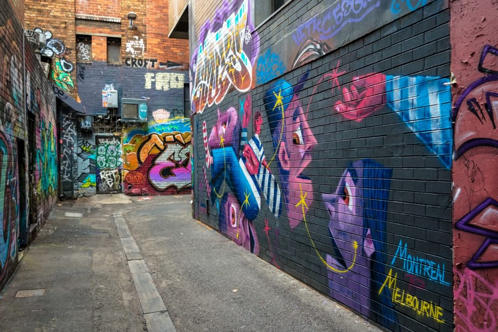 A laneway with street art murals on the wall