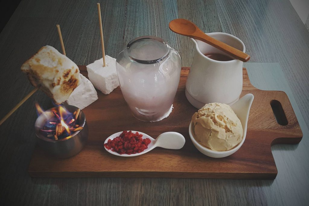 A wooden platter with various mugs and cups on it, filled with hot chocolate and immersed in smoke
