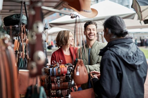 A couple talking to a stallholder at a market
