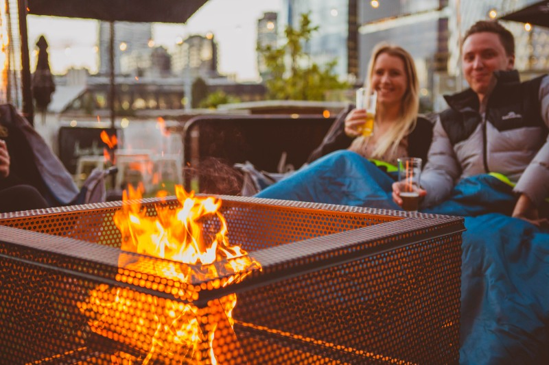 People sitting in an outdoor bar holding drinks in front of a fire