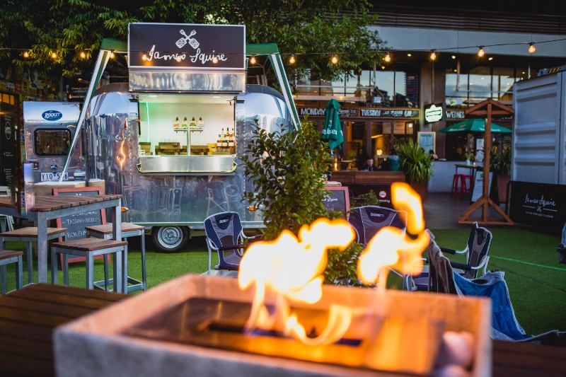 An outdoor bar with a airstream trailer as a beer bar, and a heater with flames