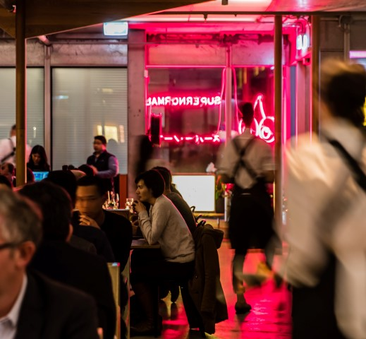 People in a crowded restaurant with a neon sign in the background