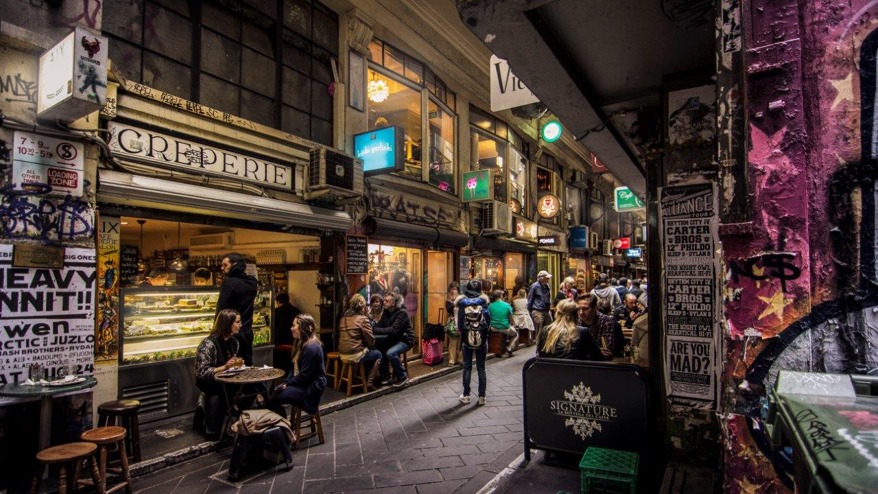 A wide shot of a bustling city laneway with cafe and shops