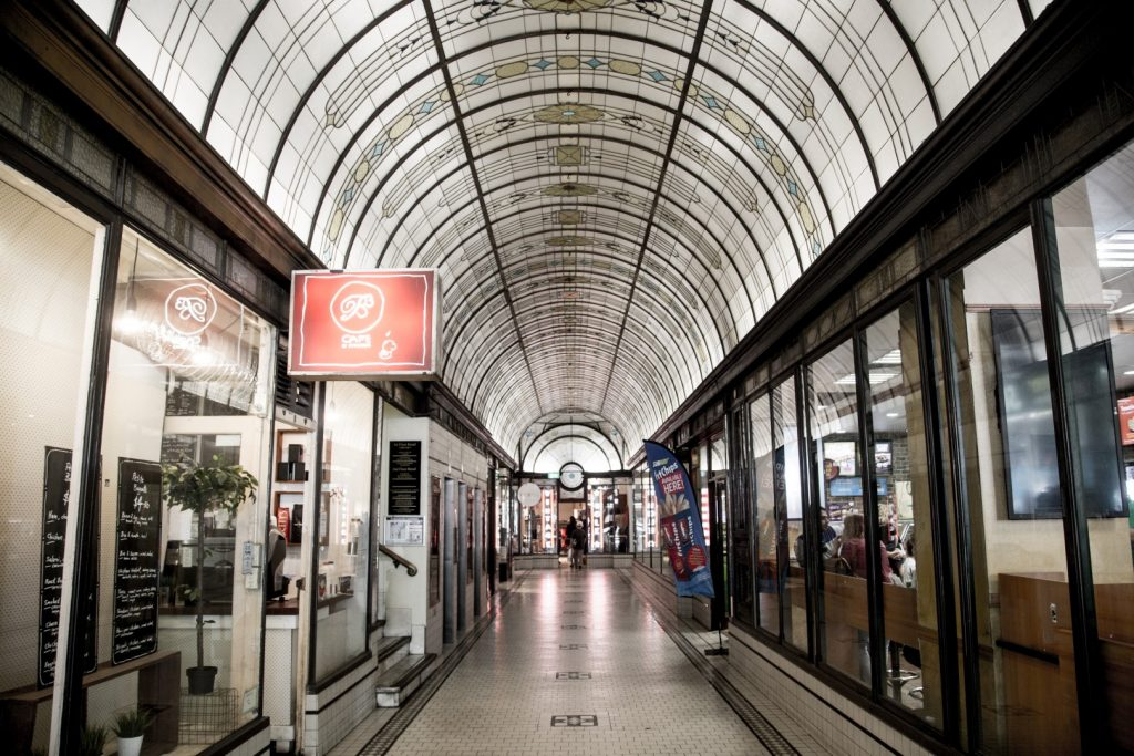 A wide laneway with shops and a domed cathedral ceiling