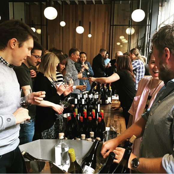 A group of people tasting wine in a bar