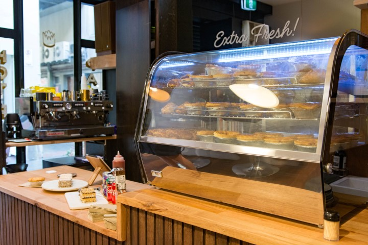 A shop counter with a display of freshly baked pies and cakes
