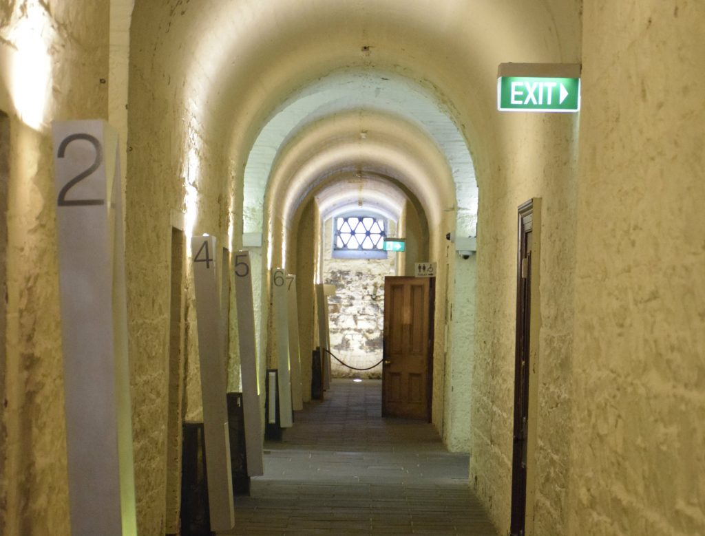A tunnel in an old building with doors along each side