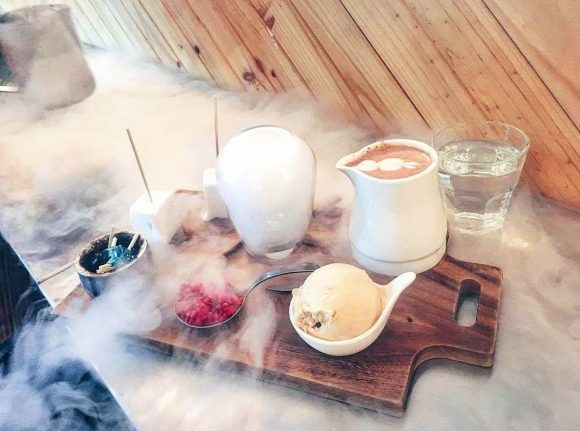 Table with chopping board filled with nitrogen icecream, berries, hot drink and other treats surrounded by smoke