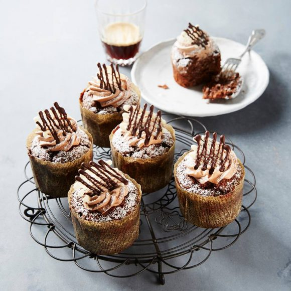 Five cupcakes on a tray, and one on a plate with a fork next to a coffee