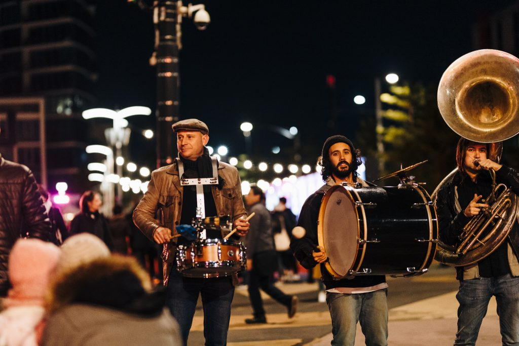 Two drummers and a trombone player performing in front of people at an outdoor festival at night