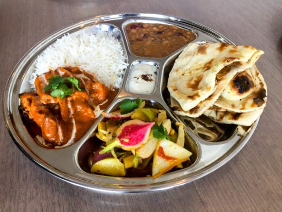 A metal tray with curry, rice, daal, pickled vegetables and roti