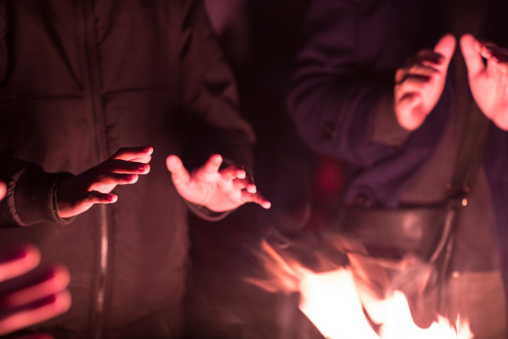 Hands warming by flames