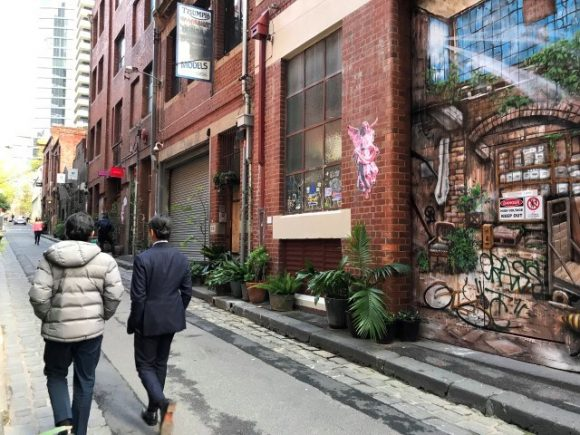 Two people walking past a street art mural in a city laneway