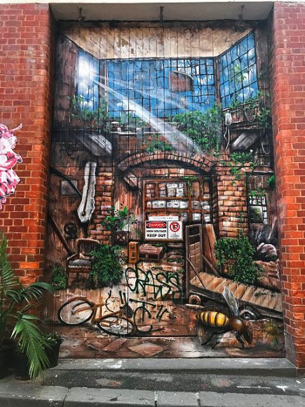 A big street street art mural paining on bricks and a door of an old building