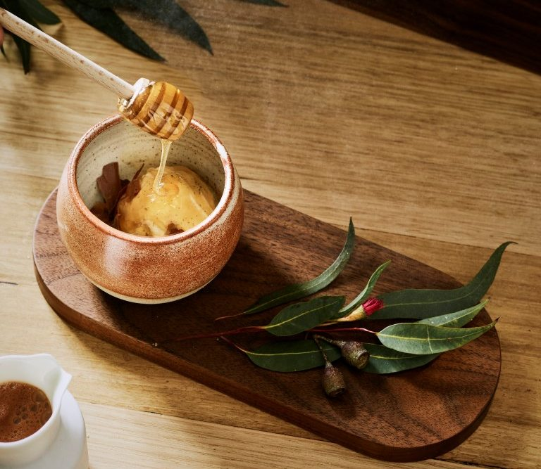 A bird's eye view of a cup on a wooden board with a honey drizzle stick inside it., and a small branch next to it.