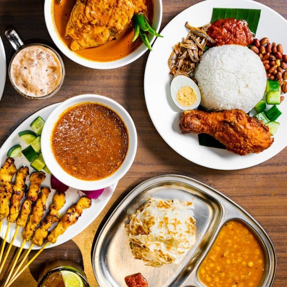 A table with lots of Malaysian dishes on it including curries and satay.