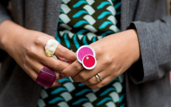 Two hands wearing four brightly coloured rings of different designs