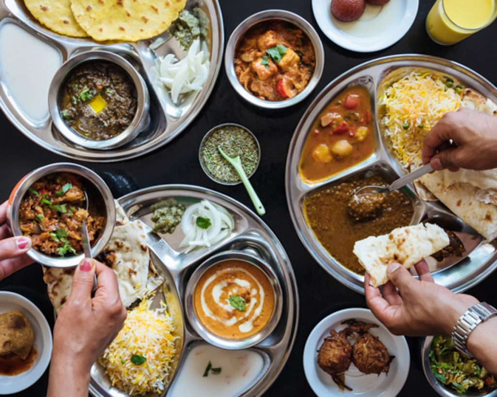 An overhead view of different Indian dishes and people reaching for food