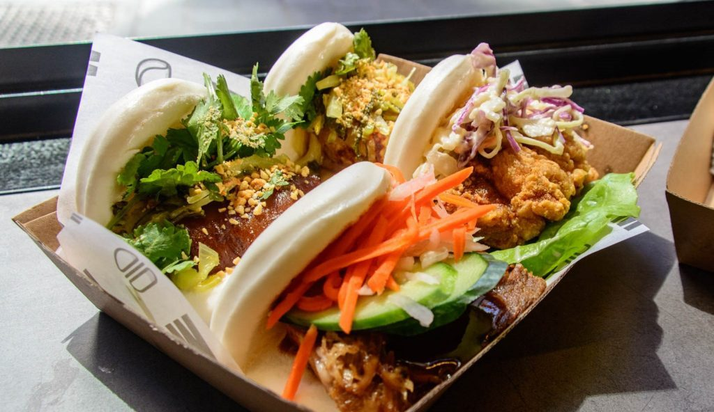 Four bao filled with salad and meat in a cardboard box