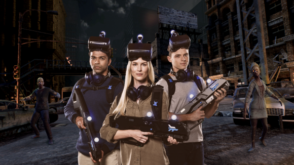 Three people wearing virtual reality glasses and carrying blasters in front of a screen with zombies