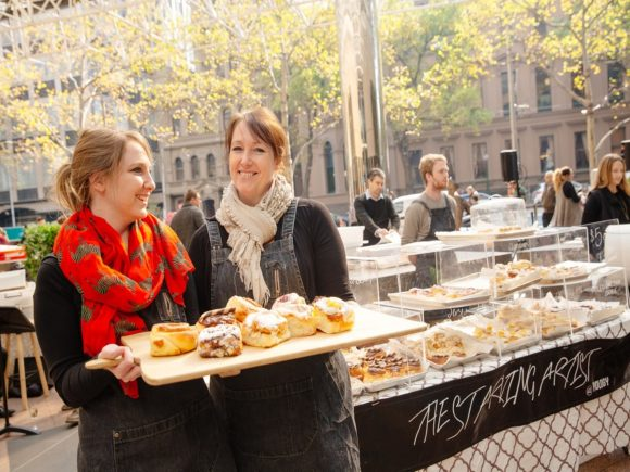 Two women holding a tray of cakes at a market
