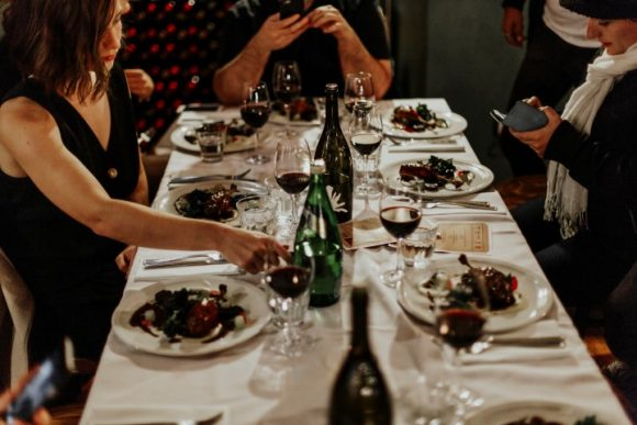 A group of people sitting at a table full of food and wine