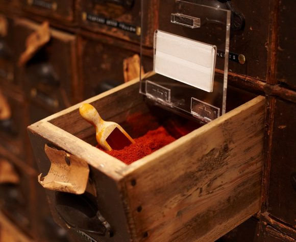 A wooden draw pulled out of a shelf with spice powder in it