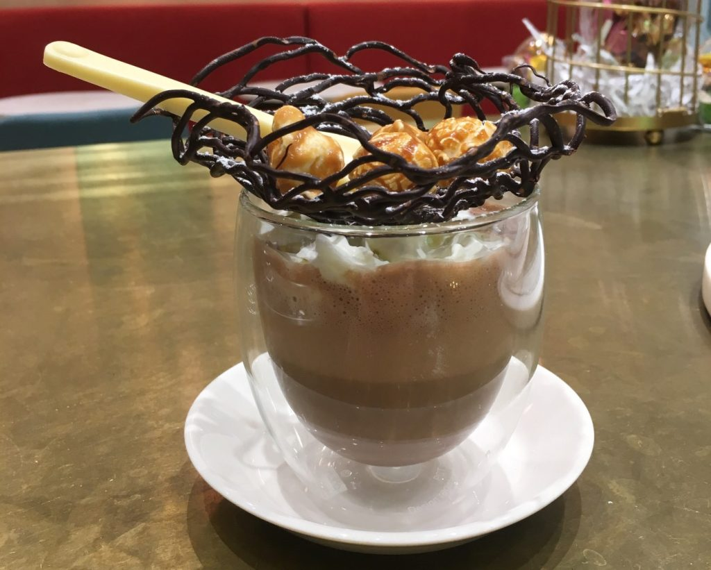 A clear glass filled with hot chocolate topped with a chocolate nest and a white spoon