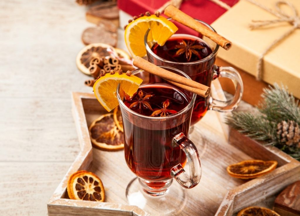 Two wine glasses full of red wine, with lemon slices and cinnamon sticks garnishing the glasses