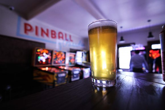 A beer on a table with pinball machines in the background