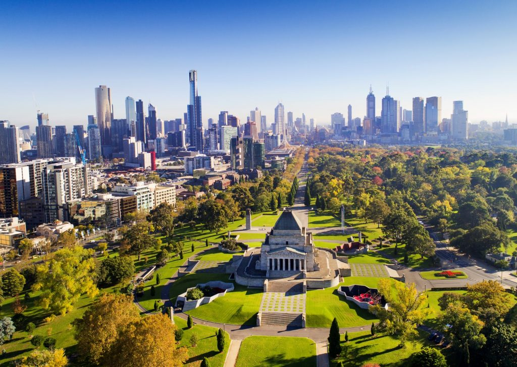An aerial shot over a city showing a large memorial shrine within expansive green parklands