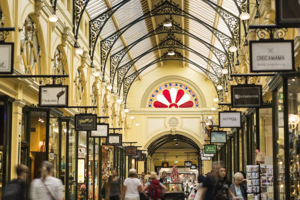 People walking along rows of shops in an old arcade