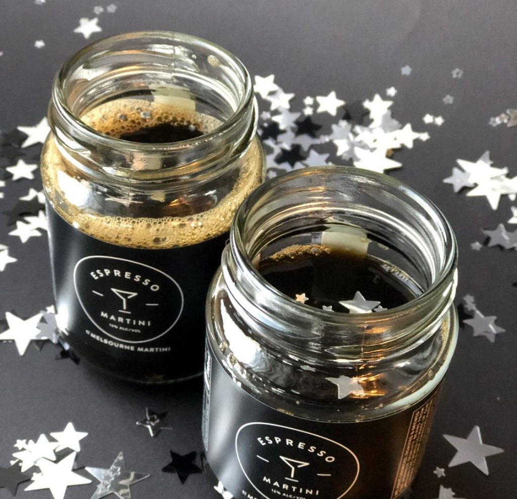 Two glasses of espresso martini cocktails on a counter covered with silver stars