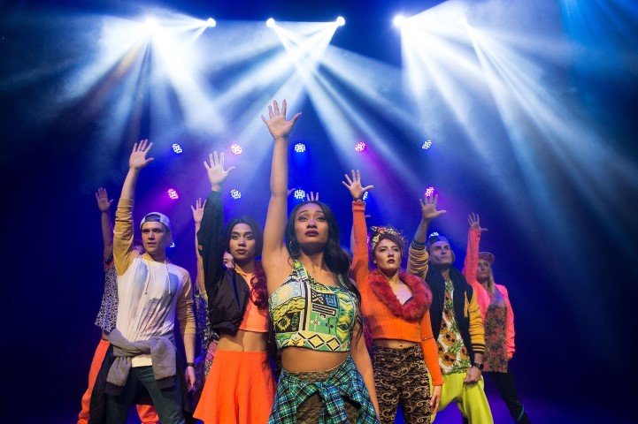 A group of people dressed as teenagers dancing under spotlights on stage