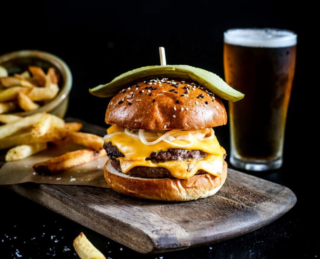 A burger, chips and a beer on a table