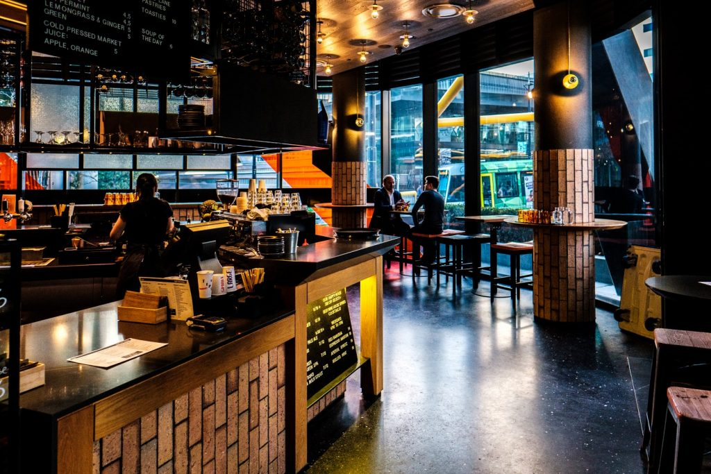 A moodily lit bar space with warm lights and large windowed doors