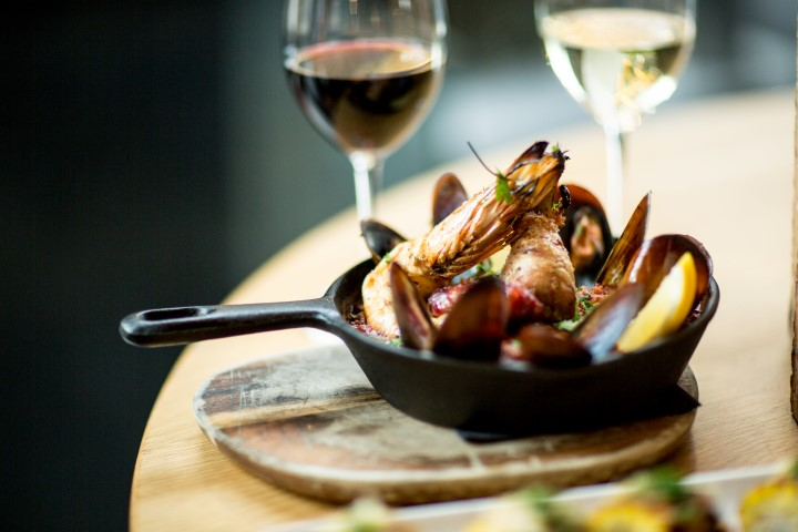 Two wine glasses behind a large skillet filled with mussels