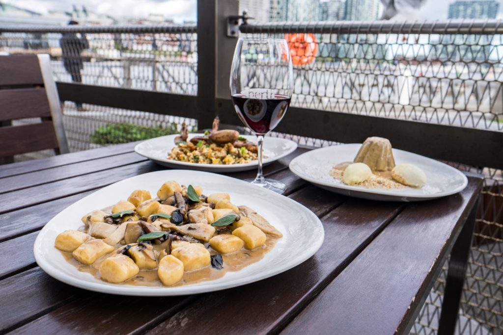 Three white dishes of Italian food on a black outdoor table