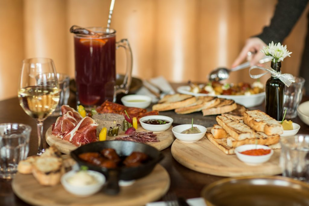 A jug of sangria, a glass of wine, and several boards with dip, bread, meats and cheese on a table