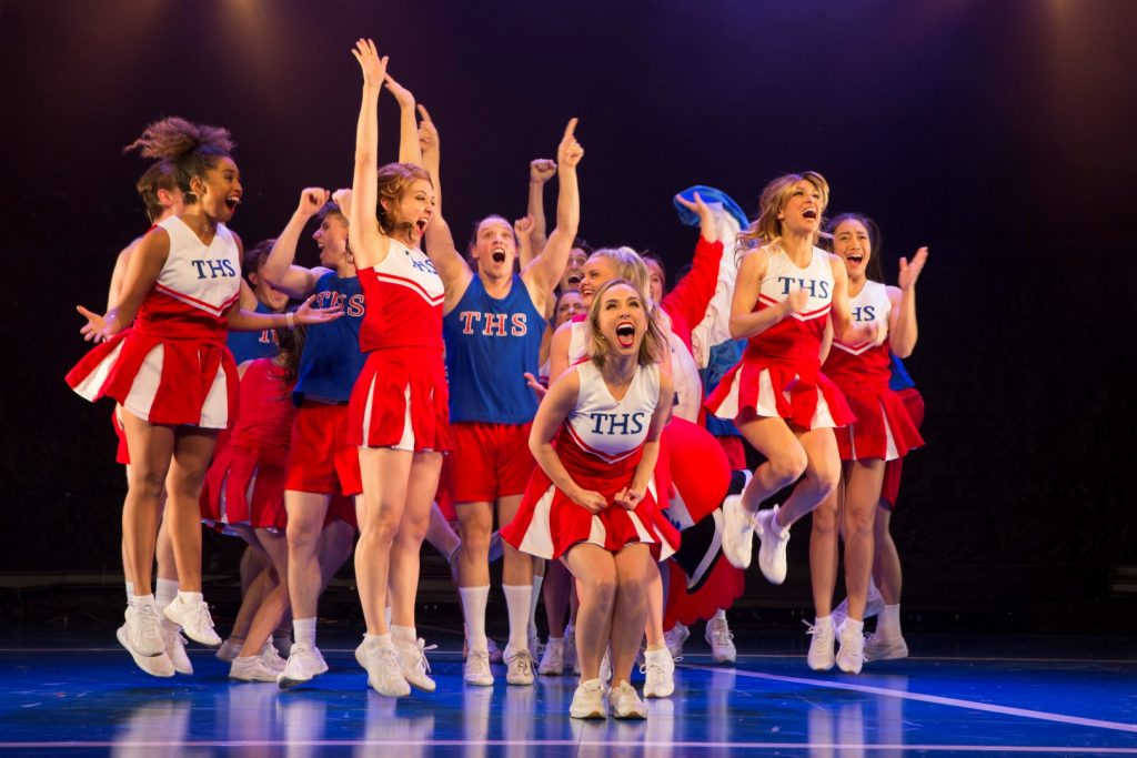 A group of performers dressed as cheerleaders on a stage