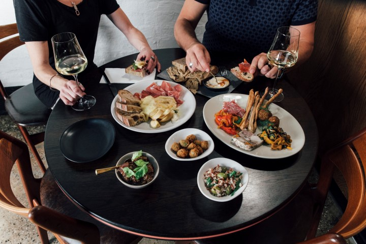 Two sets of hands picking up meats, cheese and other appetisers on a table, with two glasses of wine next to the food